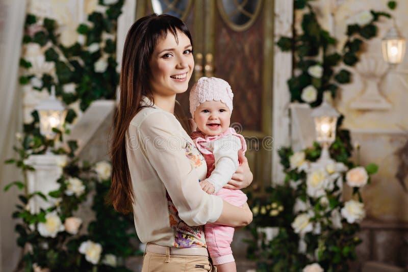 Lycklig och härlig mammabrunett som rymmer en charmig liten daugh royaltyfri foto