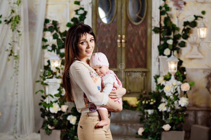 Lycklig och härlig mammabrunett som rymmer en charmig liten daugh royaltyfri bild