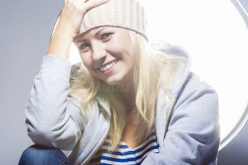 Lycklig och positiv ung Caucasian blond kvinnlig mot studio E arkivbild