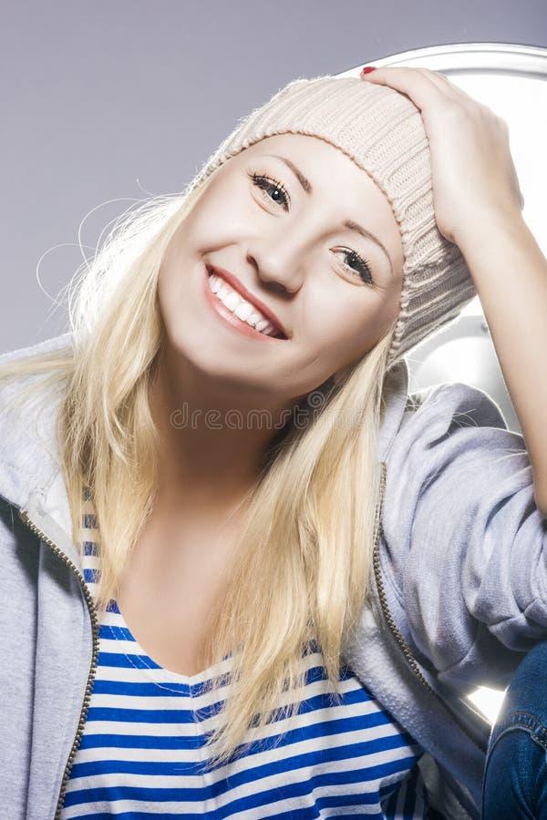 Lycklig och positiv ung Caucasian blond kvinnlig mot studio E fotografering för bildbyråer