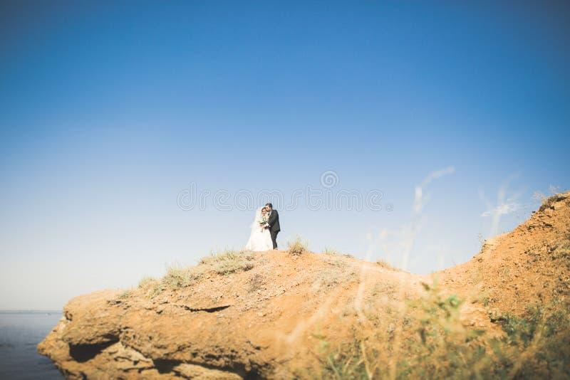 Lycklig och romantisk plats av precis gifta unga brölloppar som poserar på den härliga stranden arkivfoton