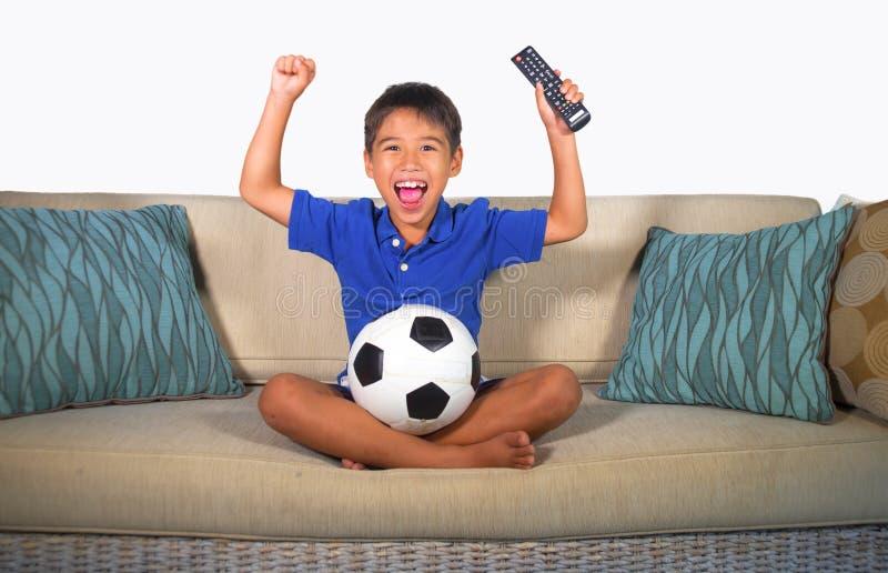 Lycklig och upphetsad hållande ögonen på fotbolllek för ung latinamerikansk pojke på hemmastadd vardagsrum för television att utt arkivfoton
