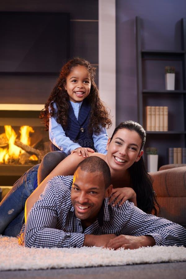 Lycklig olik familj hemma fotografering för bildbyråer