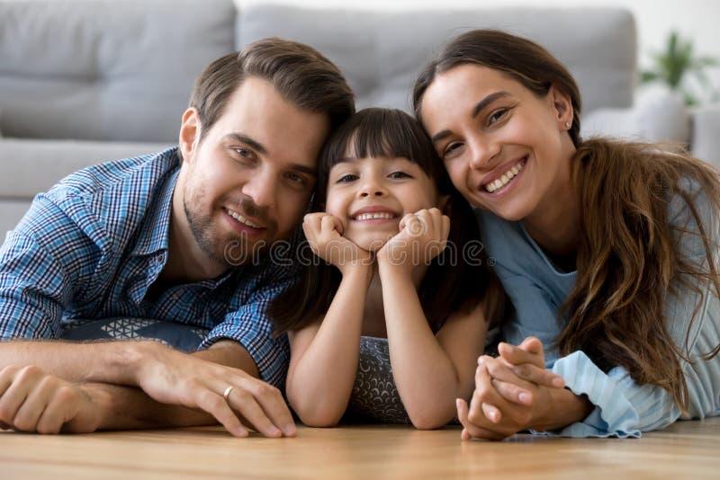 Lycklig olik familj som ligger på det varma golvet som ser kameran fotografering för bildbyråer