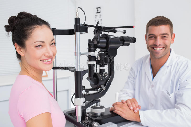 Lycklig optiker- och kvinnligpatient med den skurna upp lampan arkivfoto
