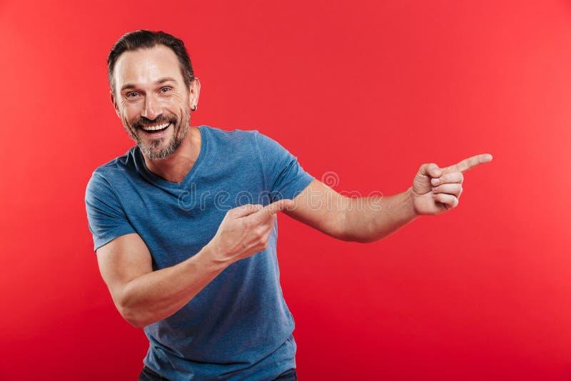 Lycklig orakad man30-tal i den tillfälliga blåa t-skjortan som pekar fingrar a royaltyfri bild