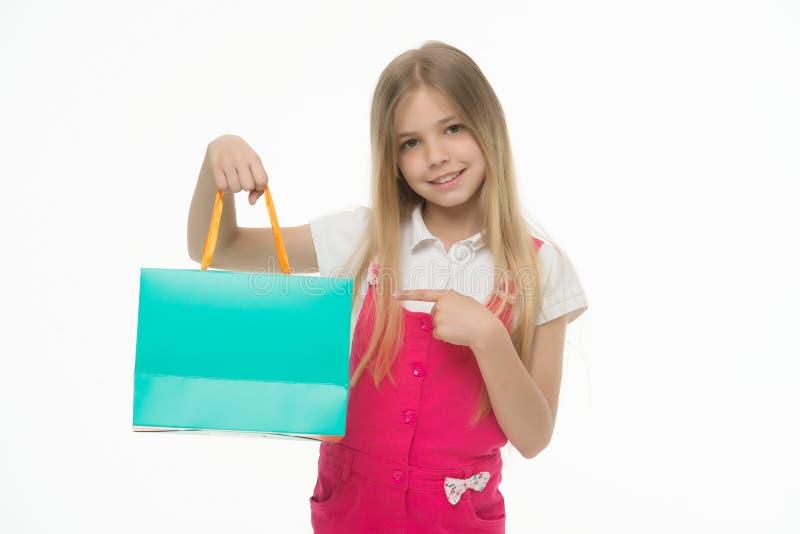 Lycklig påse för shopping för ar för barnpunktfinger som isoleras på vit Shopaholic framlägga produkt för liten flicka med den pa arkivfoton