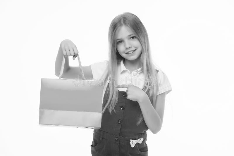 Lycklig påse för shopping för ar för barnpunktfinger som isoleras på vit Shopaholic framlägga produkt för liten flicka med den pa arkivbild