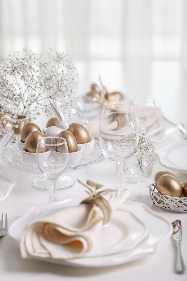 Lycklig påsk! Guld- dekor- och tabellinställning av påsktabellen med vit disk av vit färg royaltyfri bild