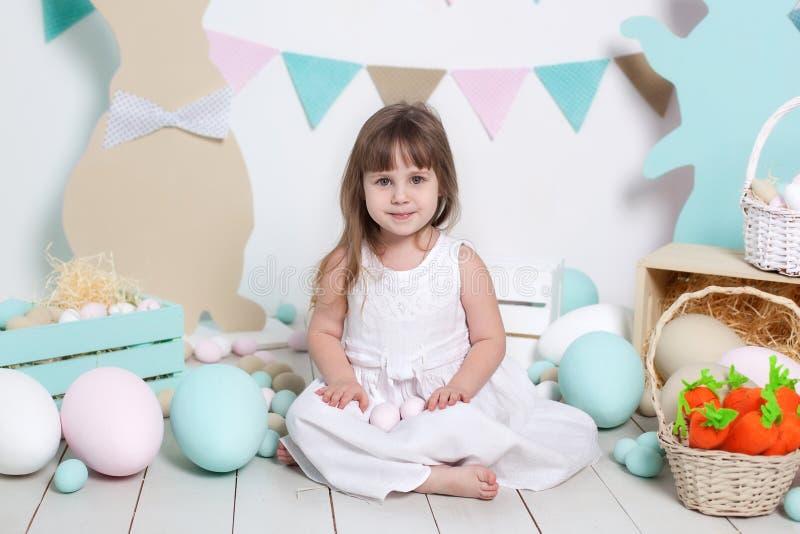Lycklig påsk! Härlig liten flicka i en vit klänning med påskägg och en korg nära de ljusa garneringarna Påskkanin och c royaltyfri bild