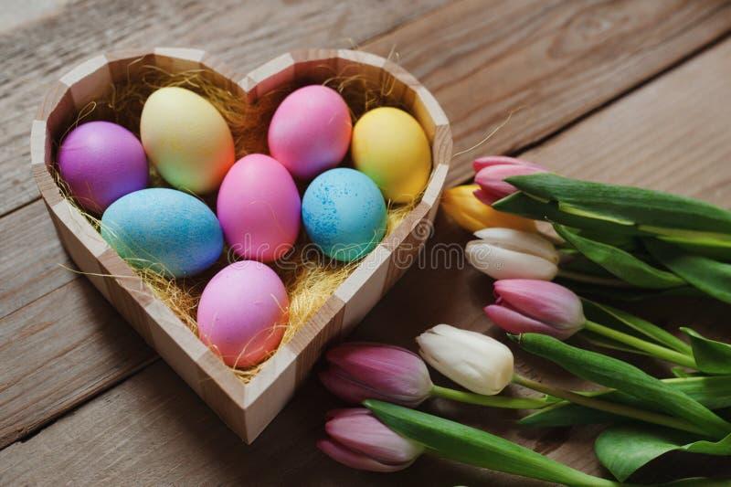 Lycklig påsk - kulöra tulpan och ägg i en formad hjärta bowlar fotografering för bildbyråer