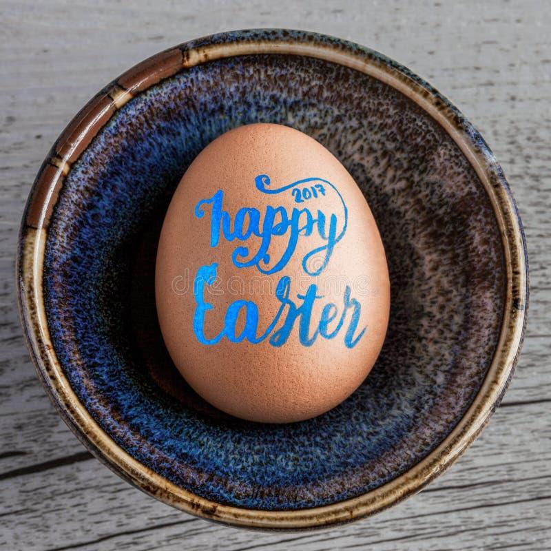 Lycklig påsk 2017 som är handskriven i blå bokstäver på äggcloseupen arkivfoto