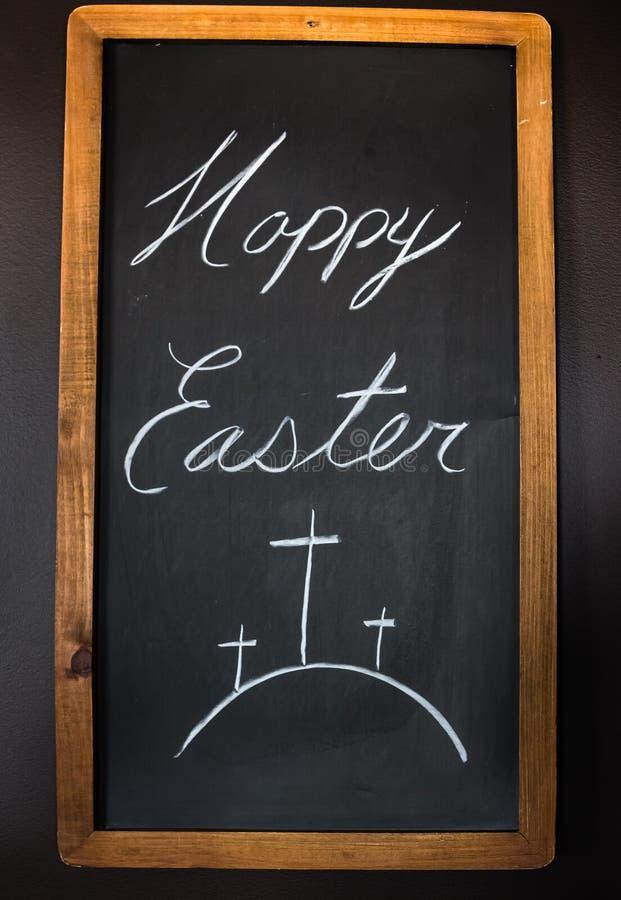 Lycklig påsk som är skriftlig på ett kritabräde royaltyfri illustrationer