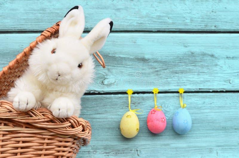 Lycklig påskkanin i korg och ägg på blå bakgrund fotografering för bildbyråer