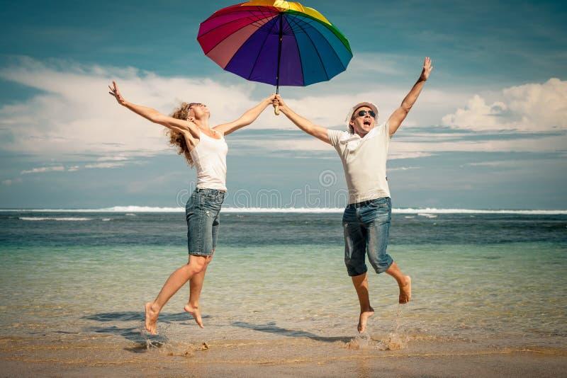 Lycklig parbanhoppning på stranden royaltyfria bilder