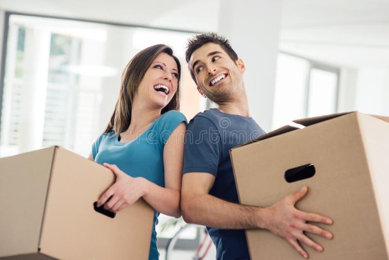 Lycklig parinflyttning deras nya hus arkivfoto