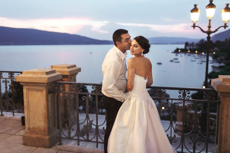 Lycklig parmake och fru som nära kramar på balkongen i afton royaltyfri foto