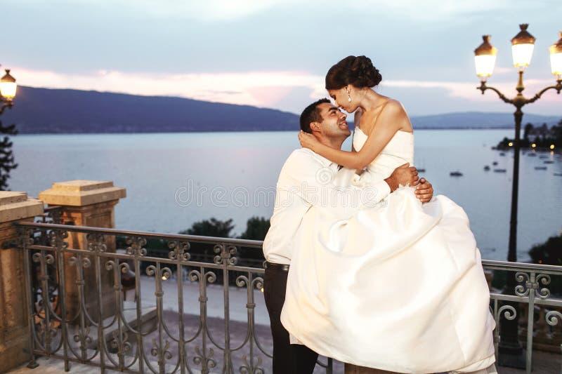 Lycklig parmake och fru som nära kramar på balkongen i afton arkivfoto