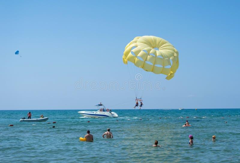 Lycklig parParasailing på den tropiska stranden i sommar Par hoppa fallskärm under hängande mitt- luft barnfadergyckel som har at royaltyfria bilder