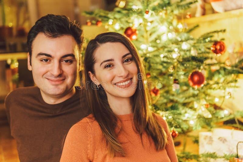 Lycklig parstående och julgran royaltyfria bilder