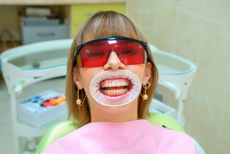 Lycklig patient för tandläkekonst i stolen i skyddsglasögon arkivbild