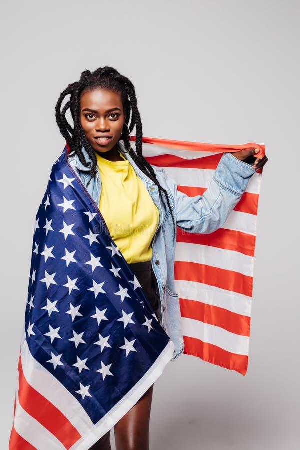 Lycklig patriotisk afrikansk kvinna som rymmer USA-flaggan, medan stå isolerat över grå färger royaltyfri foto