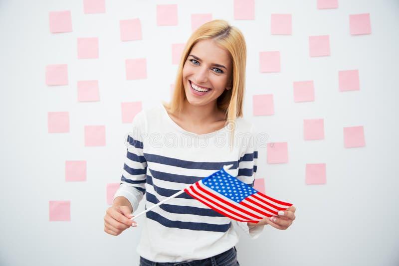 Lycklig patriotisk kvinna som rymmer USA-flaggan fotografering för bildbyråer