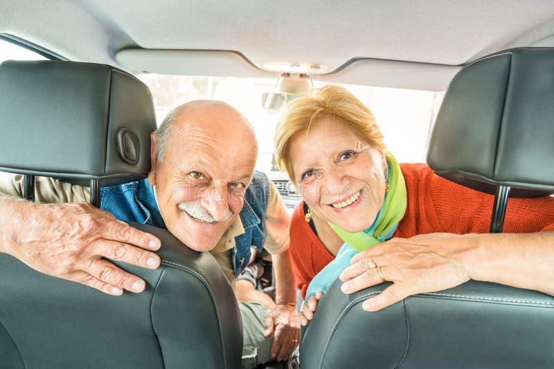 Lycklig pensionär avgick par som är klara för körning av bilen på vägtur royaltyfria foton
