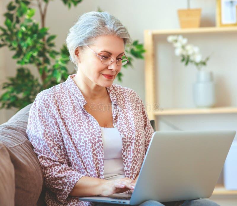 Lycklig pensionär för gammal kvinna som hemma arbetar på datorbärbara datorn arkivbild