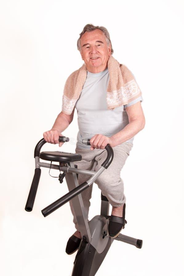 Lycklig pensionär med motionscykelen som isoleras på vit royaltyfria bilder