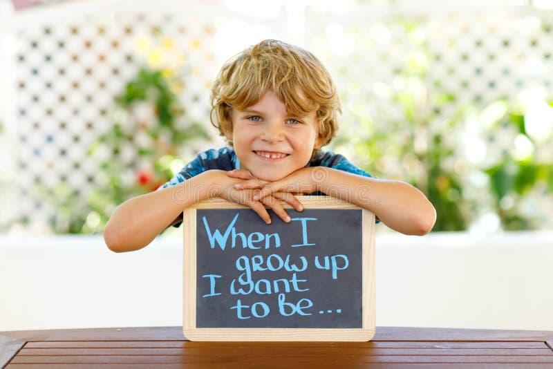Lycklig pojke för liten unge med kritaskrivbordet i händer Det sunda förtjusande barnet på skrivbordet, när jag växer upp mig, ön arkivbilder