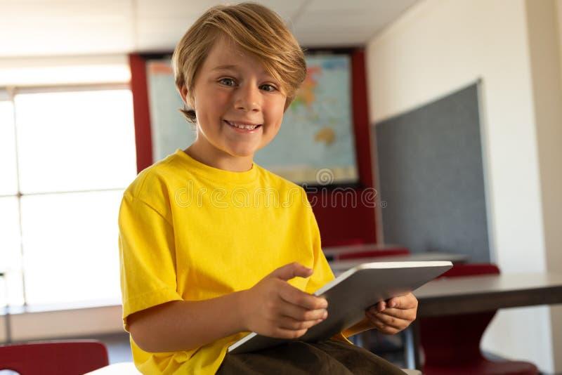 Lycklig pojke med den digitala minnestavlan som sitter över skrivbordet och ser kameran i ett klassrum arkivfoton