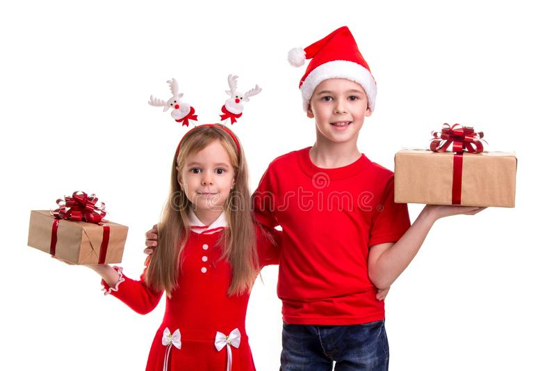Lycklig pojke med den santa hatten på hans huvud och en flicka med hjorthorn som rymmer gåvaaskarna i deras händer Begrepp royaltyfria foton