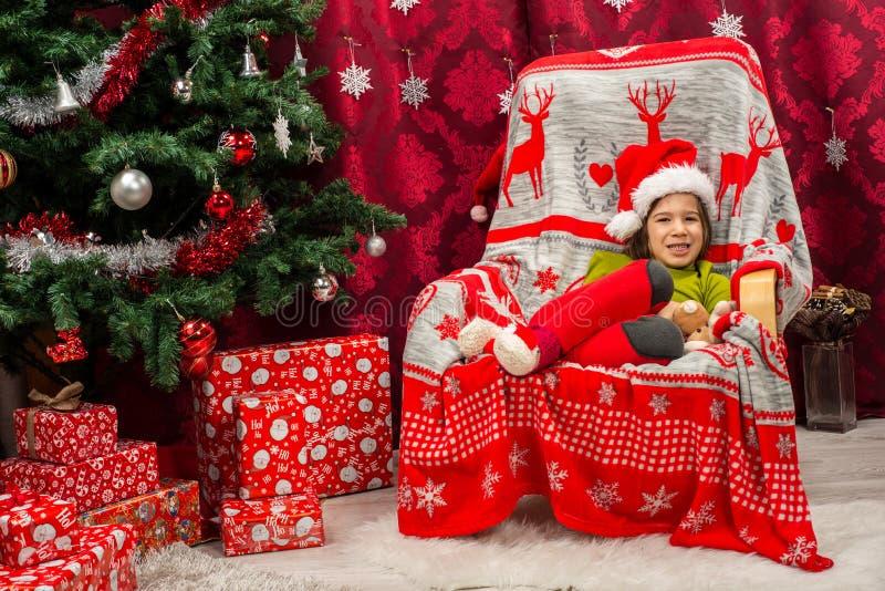Lycklig pojke med jultomtenhatten som sitter i stol arkivbild