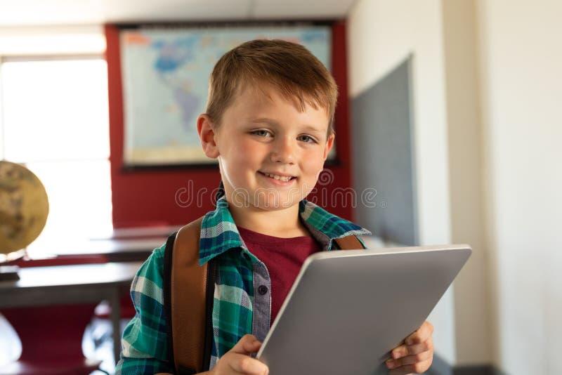 Lycklig pojke med skolapåsen och den digitala minnestavlan som ser kameran i ett klassrum royaltyfria foton