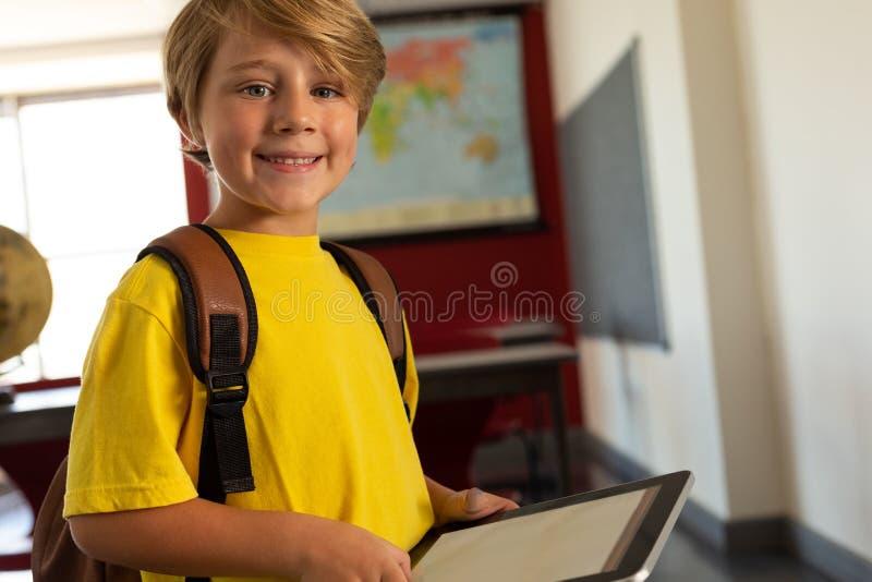 Lycklig pojke med skolapåsen och den digitala minnestavlan som ser kameran i ett klassrum arkivfoton
