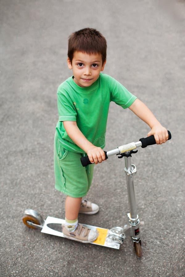 Lycklig pojke med sparkcykeln royaltyfri fotografi
