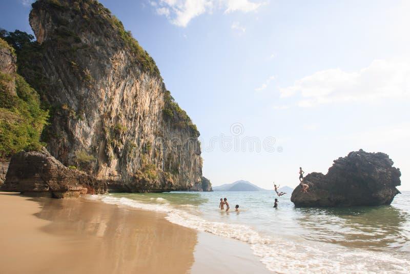Lycklig pojke- och flickabanhoppning och spela i havet under sommar arkivbild
