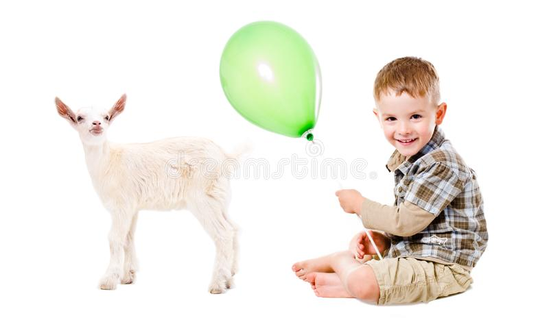 Lycklig pojke och liten get som spelar med en ballong royaltyfria bilder