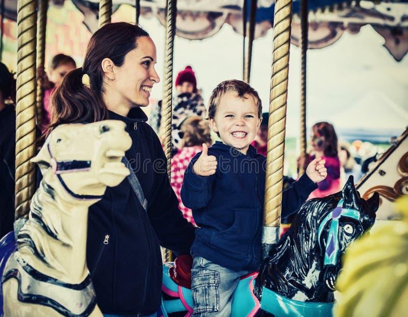 Lycklig pojke och moder på den Retro karusellen - arkivfoton