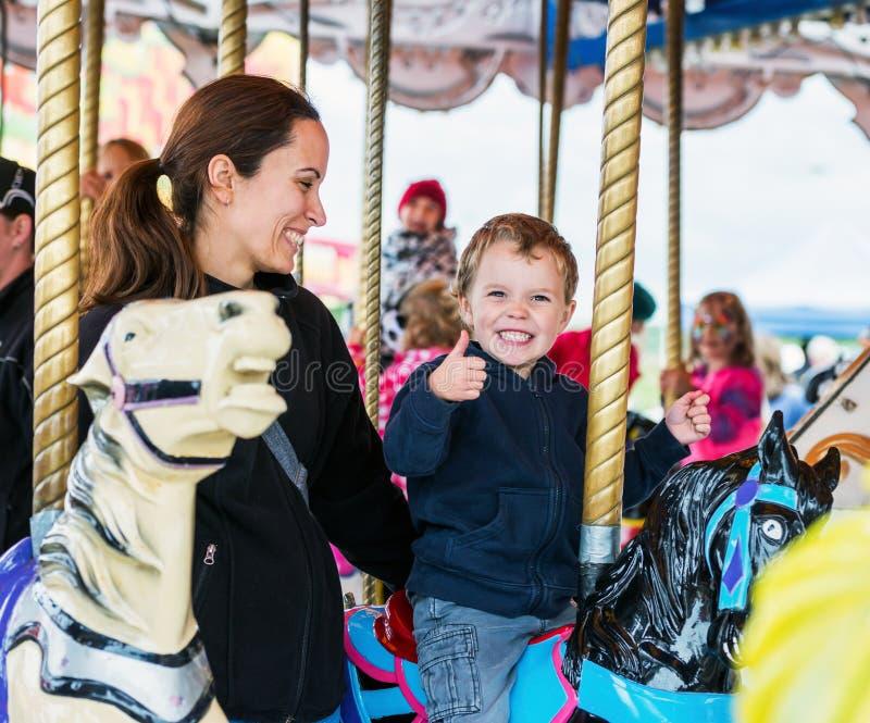 Lycklig pojke och moder på karusell royaltyfri foto