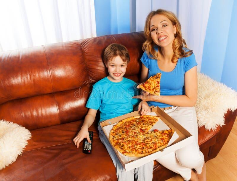 Lycklig pojke och moder som äter pizza på soffan royaltyfria foton