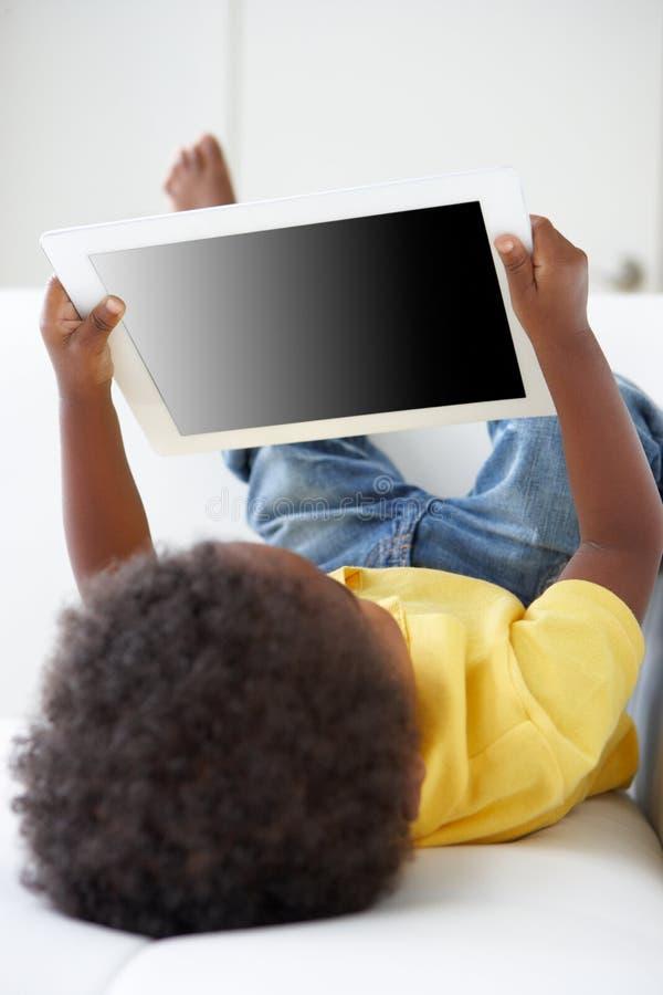 Lycklig pojke på Sofa Playing With Digital Tablet arkivbild