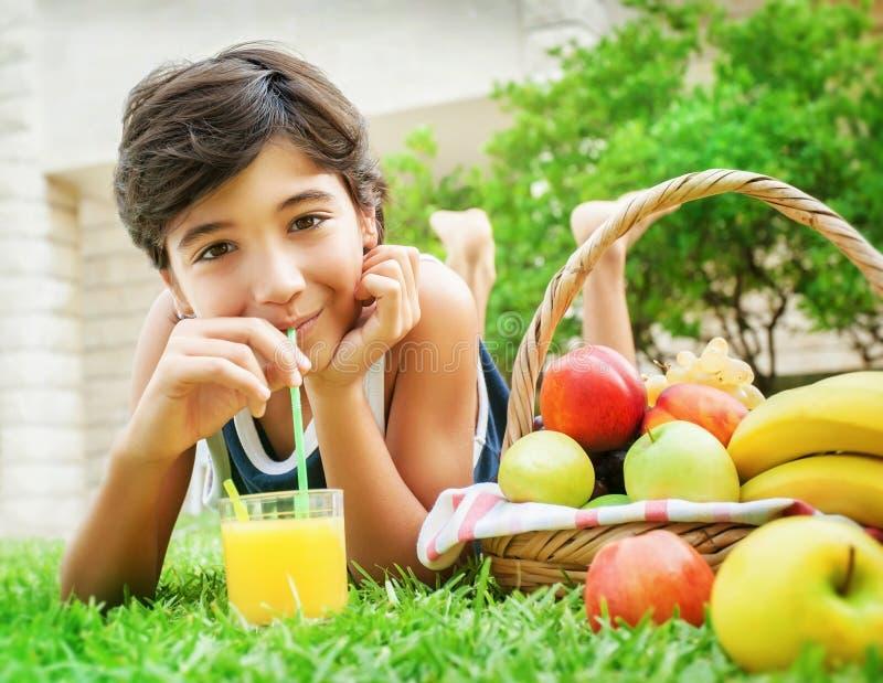Lycklig pojke som dricker fruktsaft arkivfoto