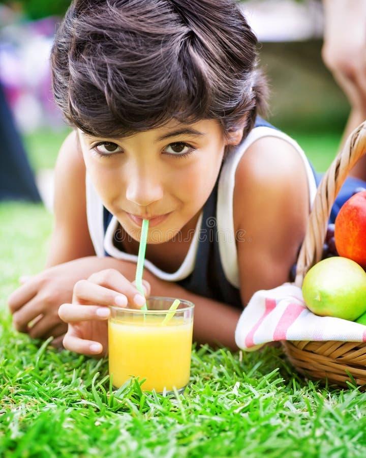 Lycklig pojke som dricker fruktsaft royaltyfria foton