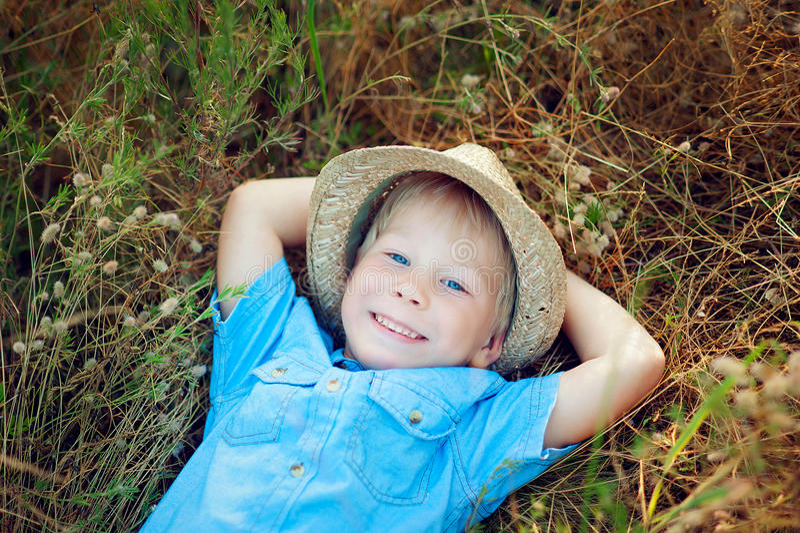 Lycklig pojke som ligger på gräset royaltyfria foton