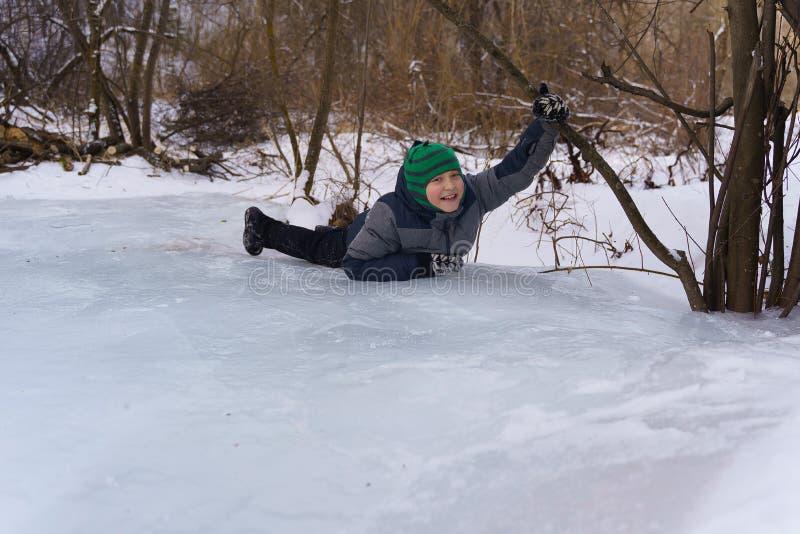 Lycklig pojke som ligger på isen i eftermiddagen i vinter arkivfoton