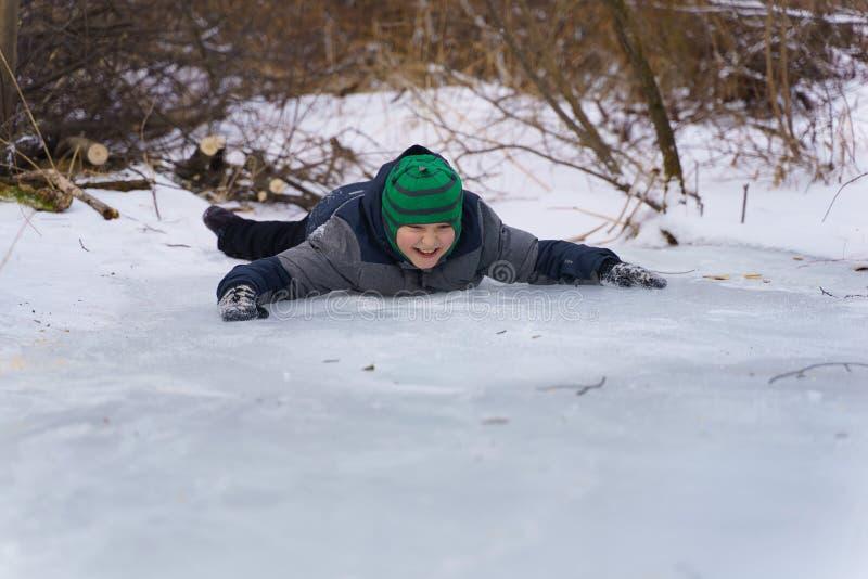 Lycklig pojke som ligger på isen i eftermiddagen i vinter royaltyfri fotografi