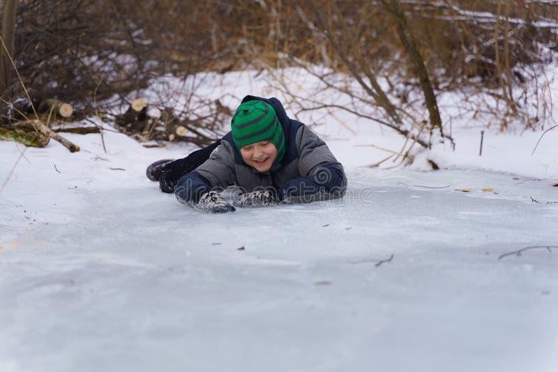 Lycklig pojke som ligger på isen i eftermiddagen i vinter royaltyfria foton