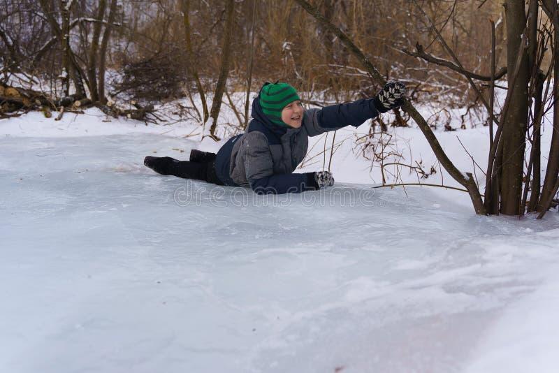 Lycklig pojke som ligger på isen i eftermiddagen i vinter fotografering för bildbyråer